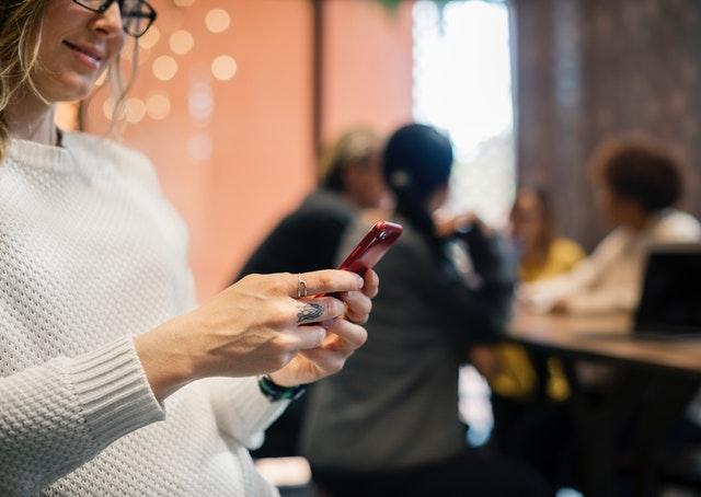 Žena, ktorá sa pozerá do červeného smartphonu.jpg