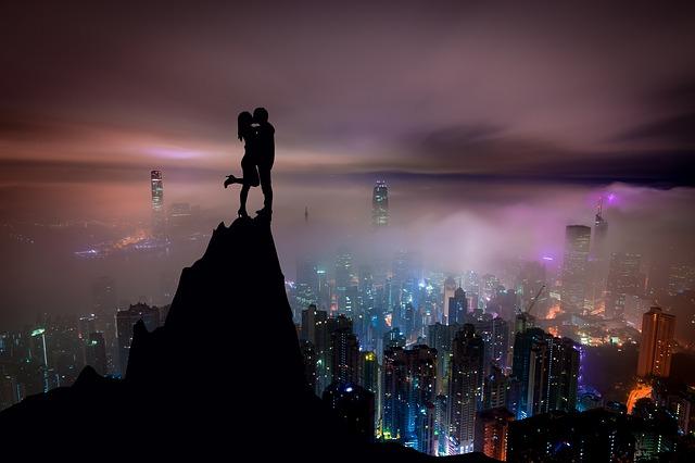 Muž a žena sa bozkávajú na vrchole kopca s panorámou rozsvieteného mesta za nimi.jpg