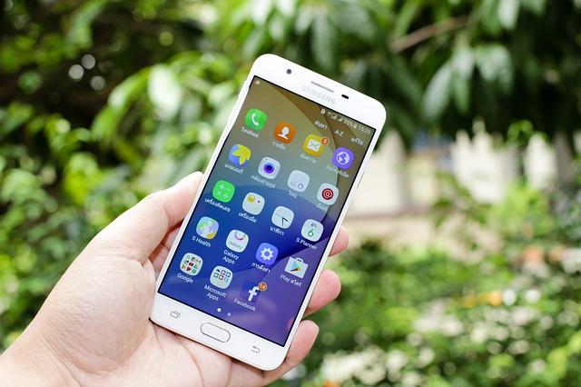 Ruka drží biely smartphone Samsung, Android, pracovná plocha.jpg