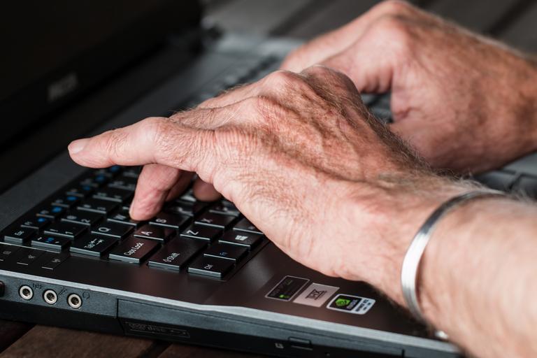 Laptop, ruky na klávesnici